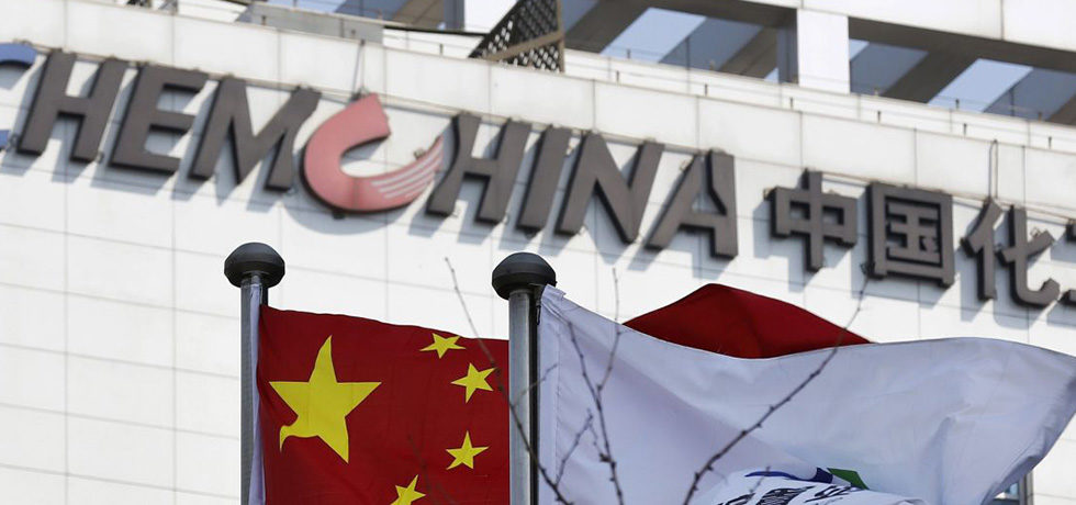 epa04676658 A Chinese national flag and a company flag fly in front the logo of China National Chemical Corporation (ChemChina) at the facade of the company's headquarters building in Beijing, China, 24 March 2015. Italy's well-known Pirelli tyre maker on 23 MArch 2015 saw a quarter of its shares sold to China's state-owned National Chemical Corp (ChemChina) on 23 March 2015, in a deal which provides for the Chinese company to secure a controlling stake later. ChemChina subsidiary China National Tire & Rubber (CNRC) will take over the 26.2 per cent of Pirelli owned by Camfin, a holding company and current leading shareholder, for 15 euros (16.29 dollars) per share, ChemChina said. EPA/WU HONG